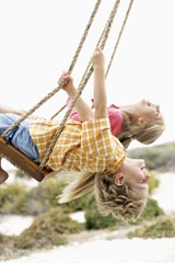 Siblings Swinging --- Image by © Royalty-Free/Corbis